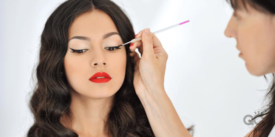 mua applying eye makeup to female model