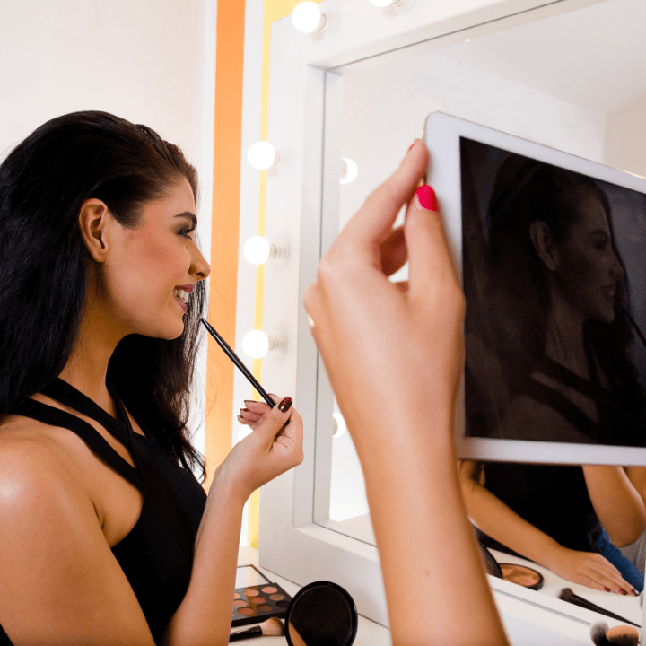 woman looking in mirror and doing makeup, while friends films on iPad