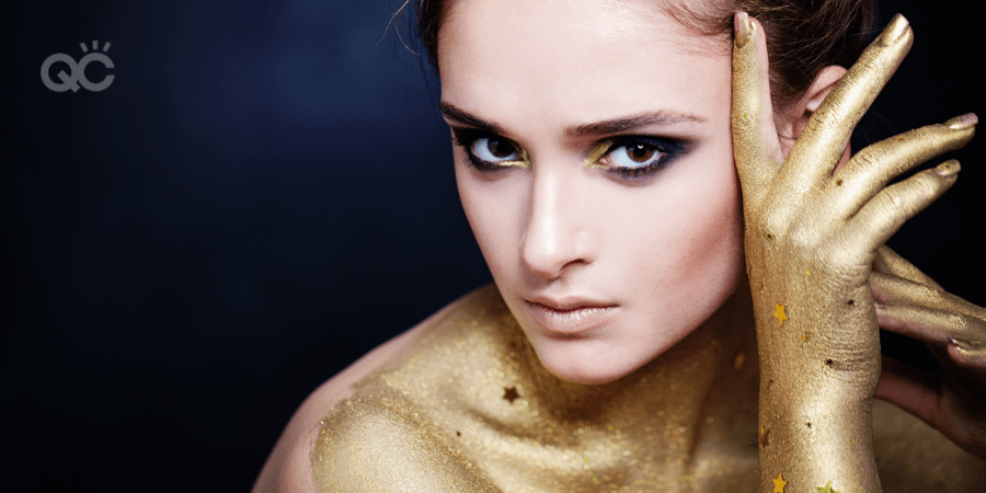 girl with smokey eye makeup covered in gold body paint