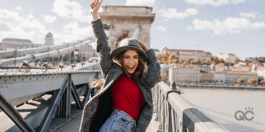 happy girl posing on bridge in front of large city
