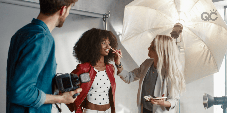 makeup artist touches up model's face on set of photoshoot
