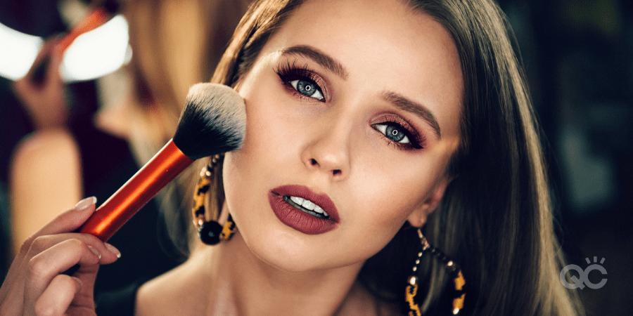 upclose of beautiful woman wearing makeup, brushing powder brush to cheek