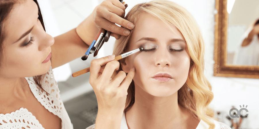 MUA applying eye makeup to model