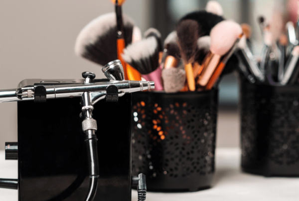 airbrush machine and regular makeup on table