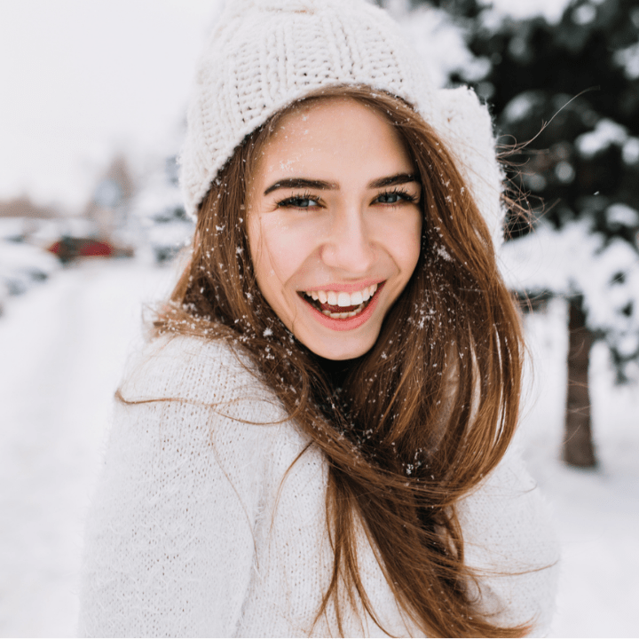 Spectacular long-haired woman laughing while posing on snow background. Outdoor close-up photo of caucasian female model with romantic smile chilling in park in winter day.