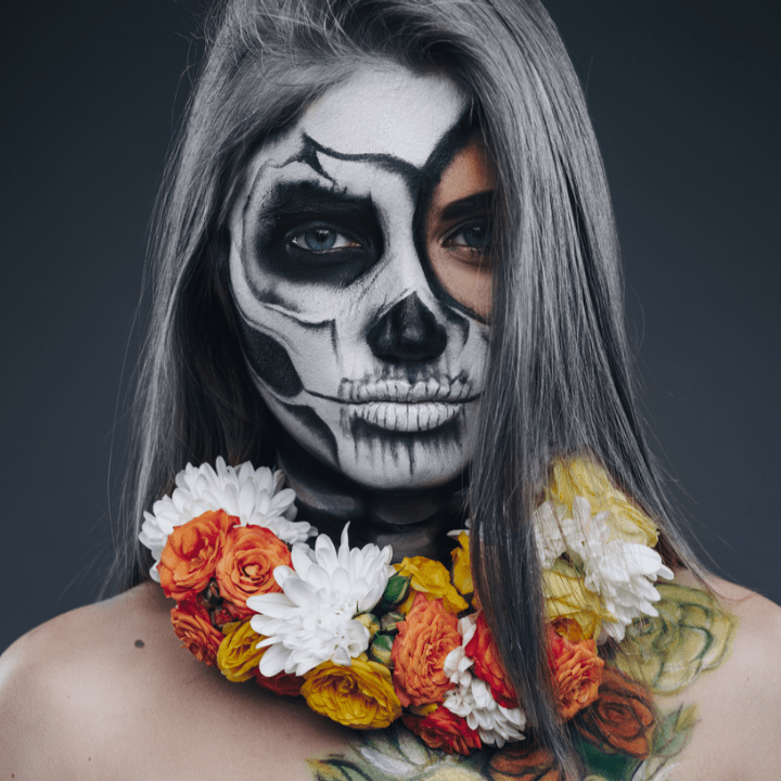 Spooky female with skeleton makeup and floral wreath on neck looking at camera during Halloween party against gray background