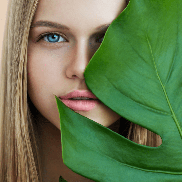Beauty smiling blonde model with natural make up and green leaves. Copy space. Spa and wellness. Close up, selective focus.