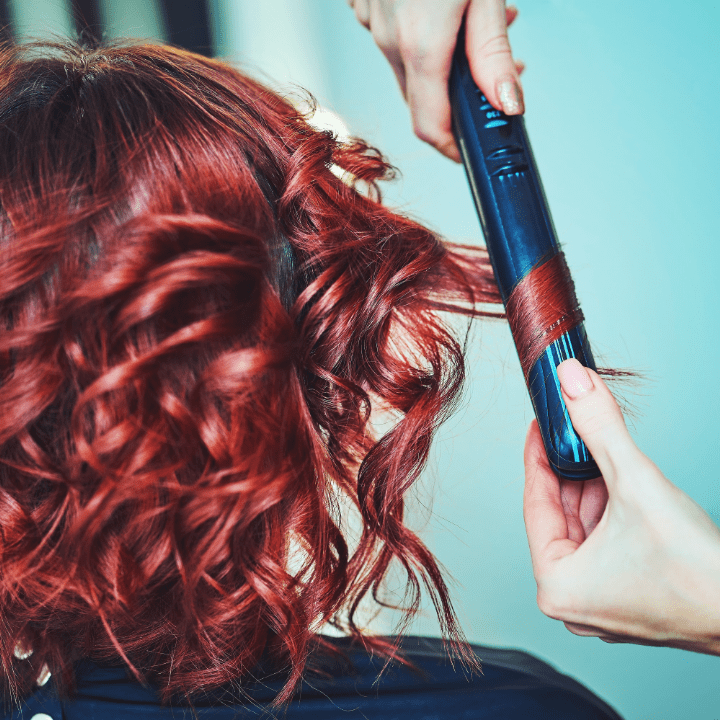 redhead having hair curled with straightener