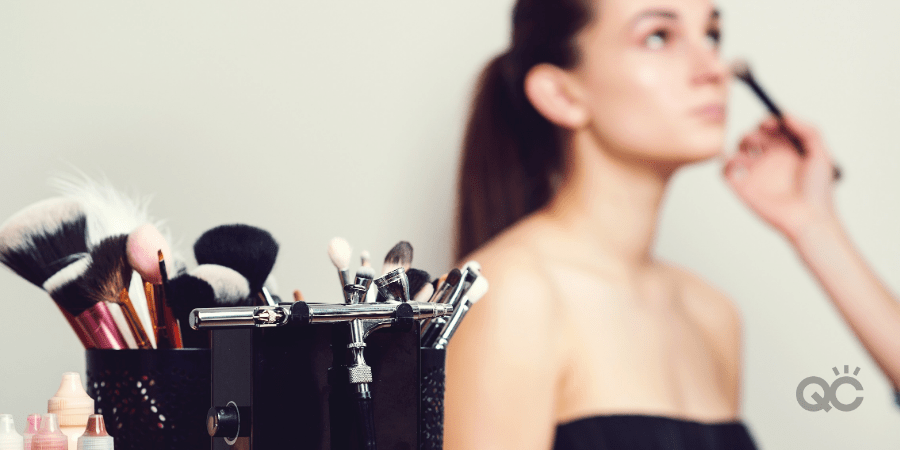 makeup tools, with model having makeup put on her in background