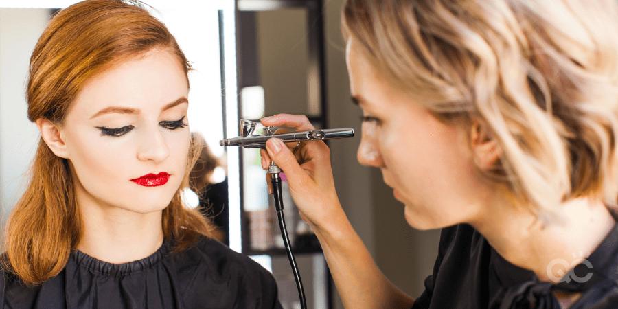 mua applying makeup on client using airbrush machine