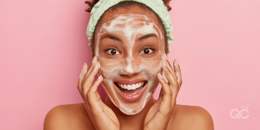 Smiling glad dark skinned young woman puts soap on face for cleansing, washes with cold water, wants to have healthy fresh skin., wears headband, looks positively at camera, stands naked indoor