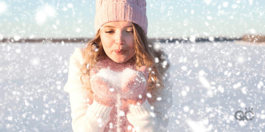 Girl blowing on the snow in the park in winter.