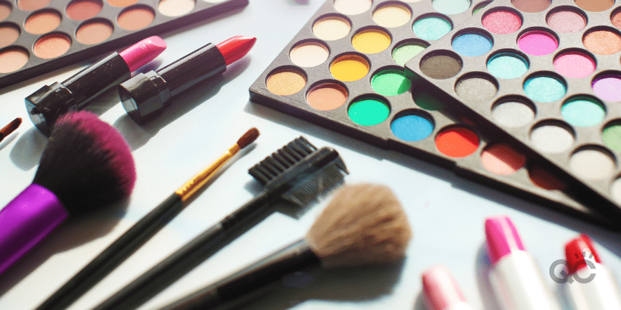 Professional make up set: eyeshadow palette, lipstick, make-up brushes and many cosmetics close up. Film and flare effect.