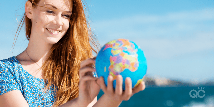 Smiling beautiful young woman standing in the summer sunshine holding a globe at the sea with copyspace