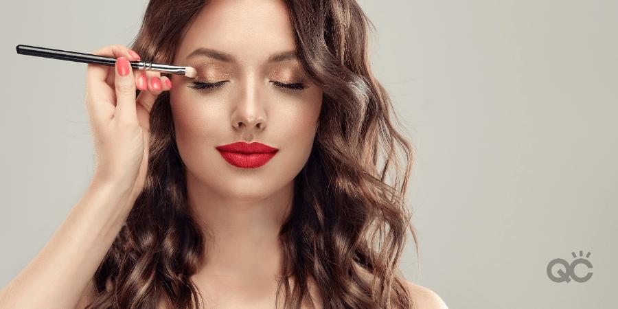 Photo of professional makeup artist's hand applying eyeshadow to model