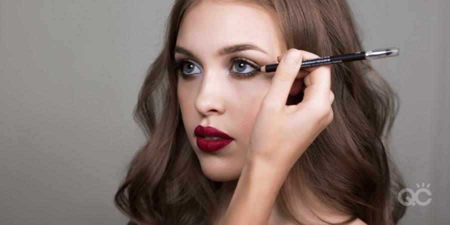 Makeup artist applying eyeliner to model - makeup artist practice article