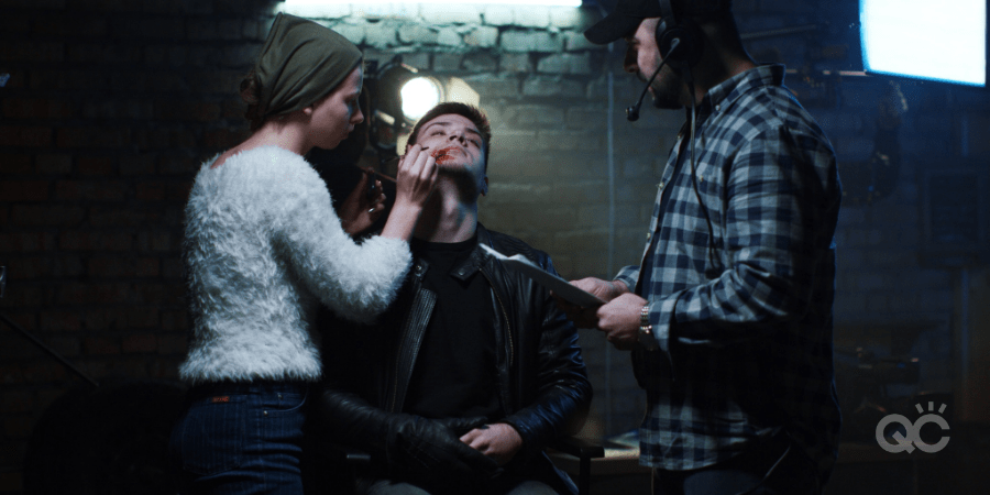 Makeup artist applying special effects makeup to actor