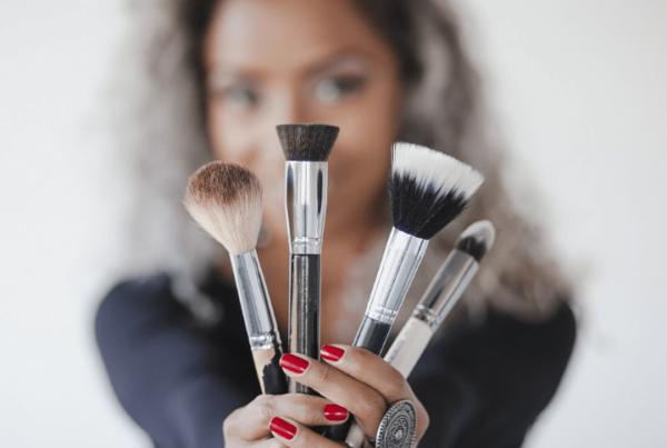 makeup artist holding up makeup brushes