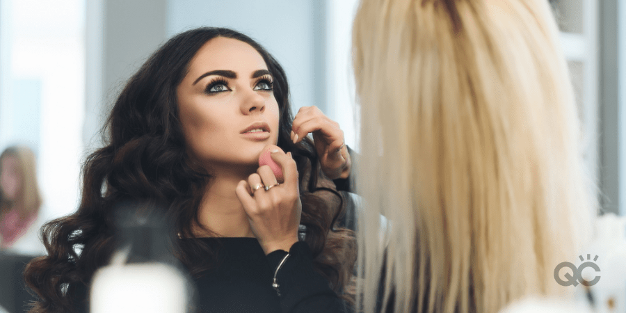 woman learning how to become a makeup artist by getting hands-on training on female model