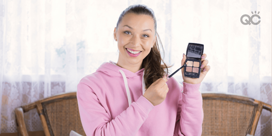 makeup artist looking at camera and holding up eyeshadow palette
