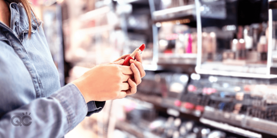 woman holding lipstick in cosmetics section of drugstore
