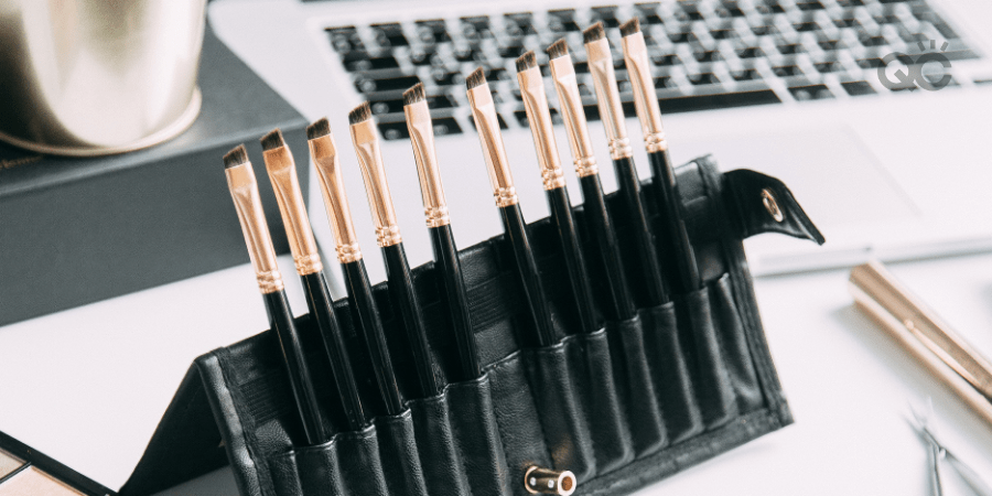 makeup brushes propped up on table in front of laptop