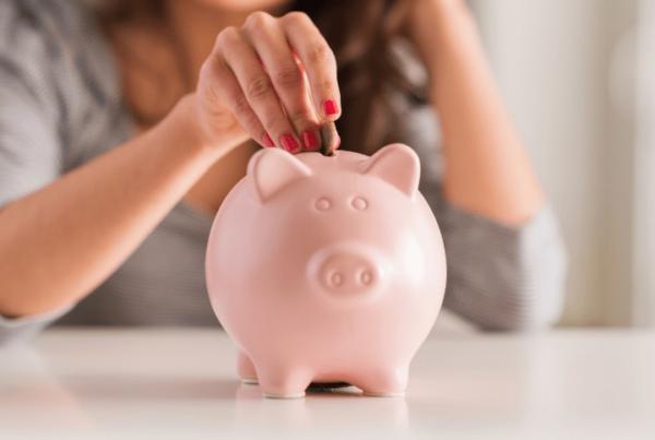 woman increasing makeup artist salary, putting money into piggy bank