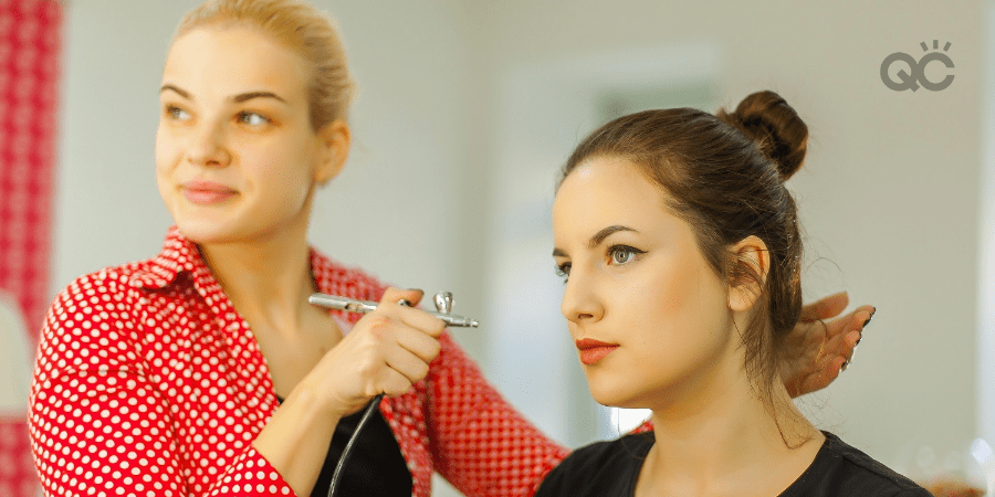 makeup artist using airbrush on client