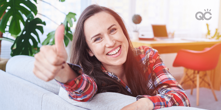 woman sitting on couch, giving thumbs up
