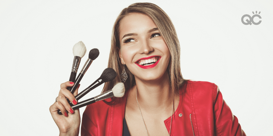 happy woman holding up makeup brushes
