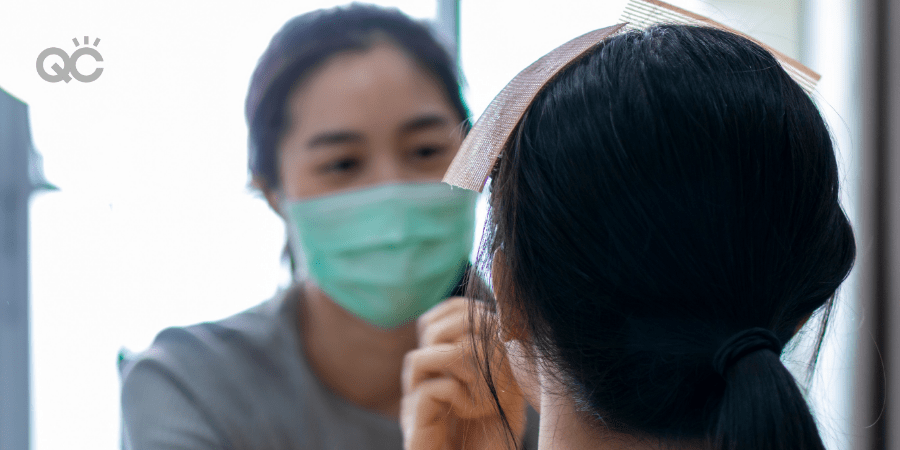 makeup artist wearing mask and applying makeup to client's face