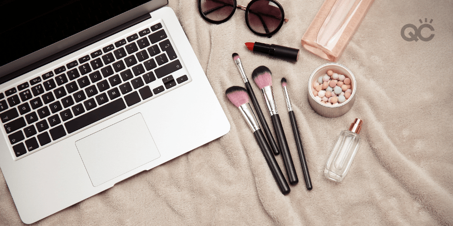 cosmetics and laptop on blanket