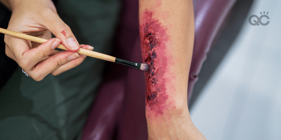MUA touching up special effects makeup on forearm