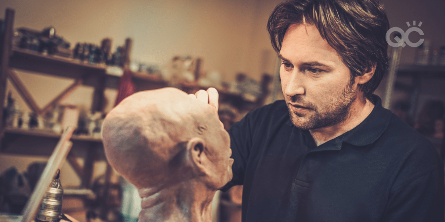 male makeup artist working on prop head