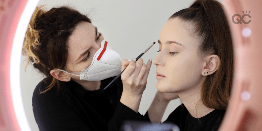 makeup artist wearing face mask and applying makeup to female client