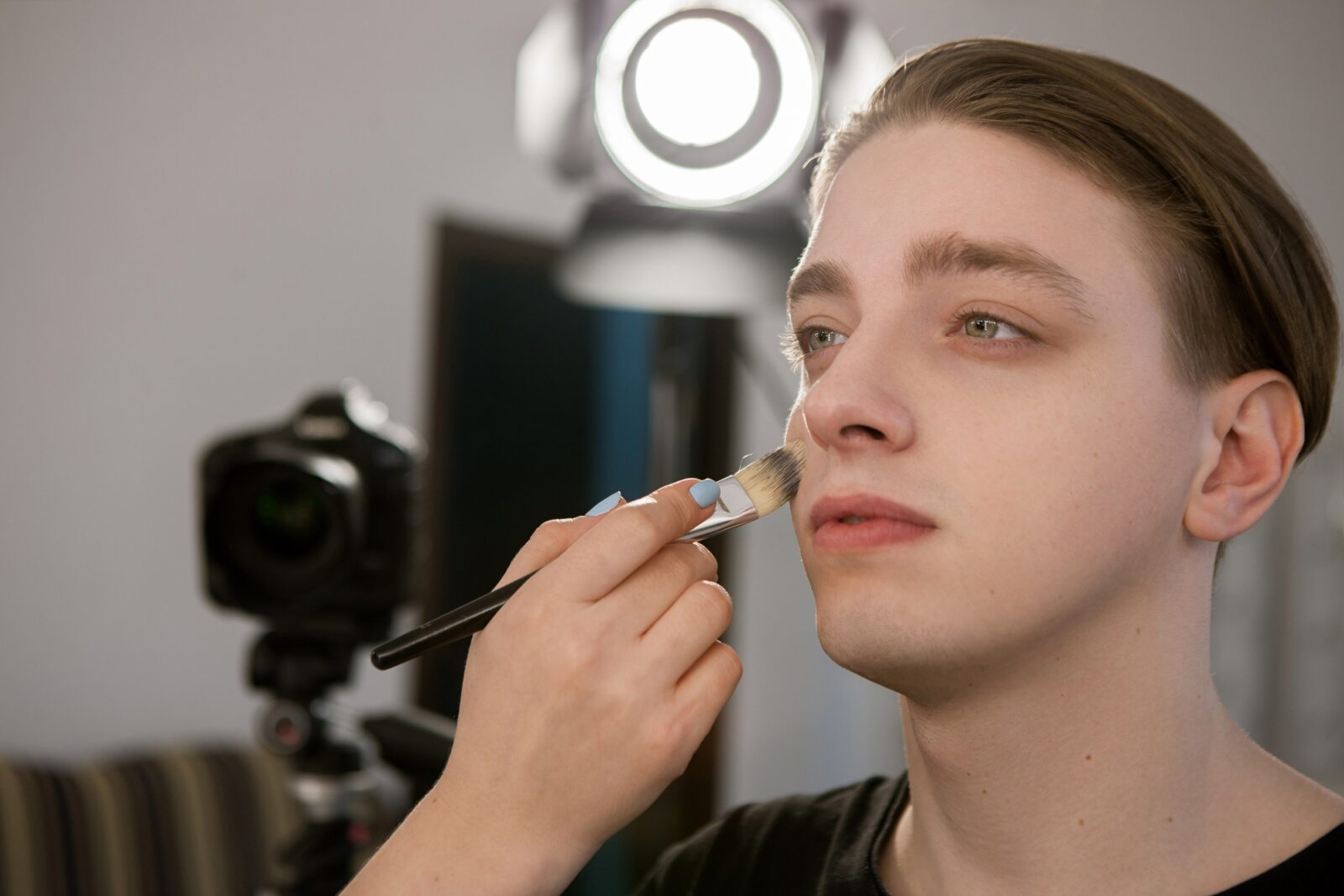 makeup artist putting makeup on male model's face
