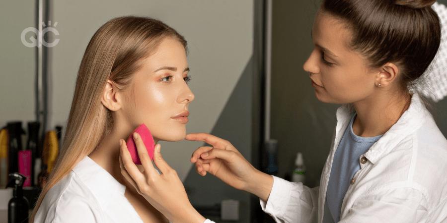 makeup artist applying makeup to model with beauty blender