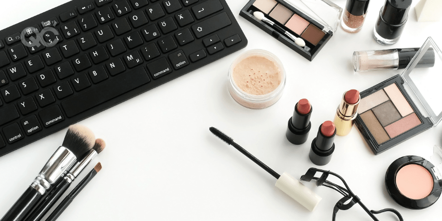makeup on table with laptop keyboard