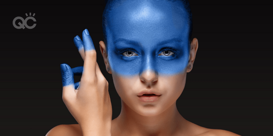 model with bright blue makeup on face and fingertips