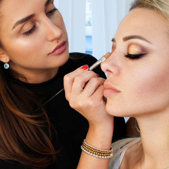 Makeup artist applying gold eyeshadow to model - makeup artist salary article