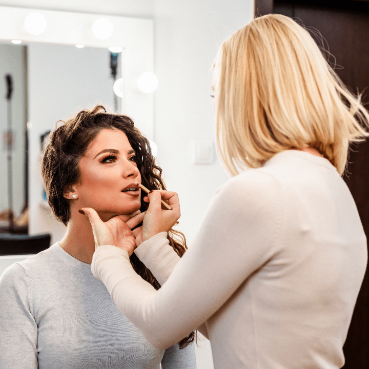 makeup artist jobs article, mar 30 2021, feature image, makeup artist working on client