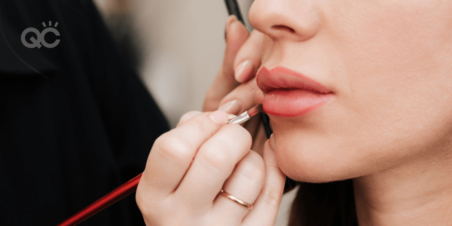 makeup artist applying lip product to model's lips
