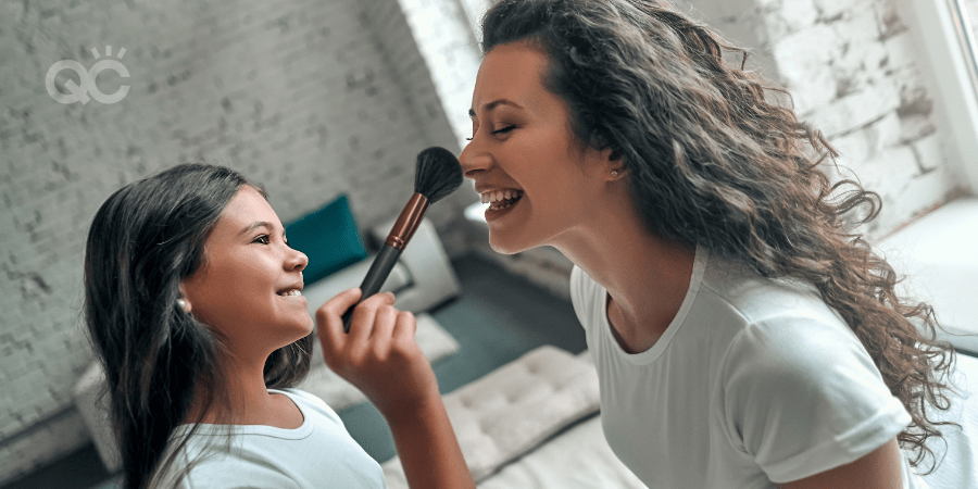 mother becoming a makeup artist at home, daughter brushing nose with makeup brush