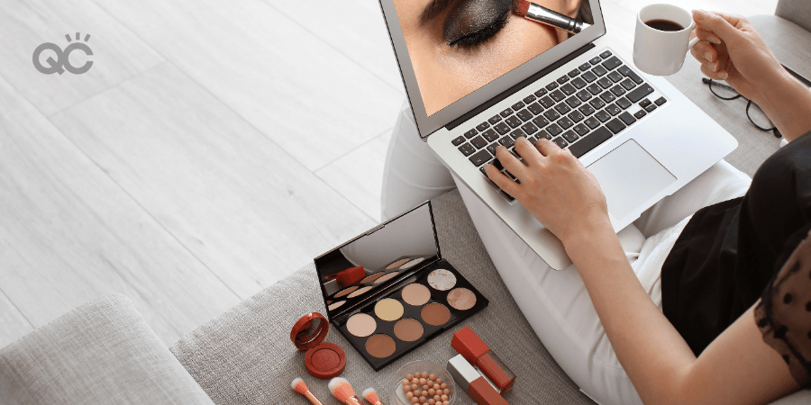 woman watching makeup lesson on laptop, sitting on couch with makeup products laid out next to her
