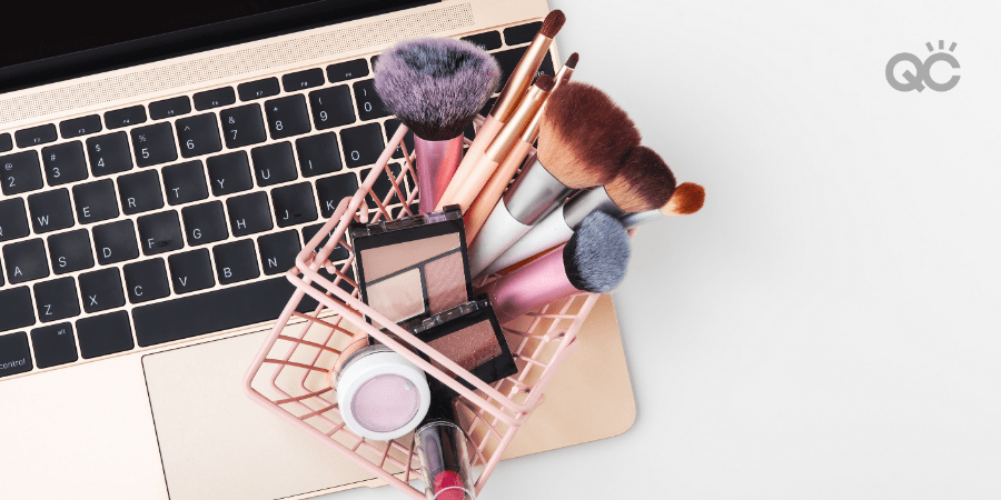 makeup products in mini shopping basket, sitting on laptop