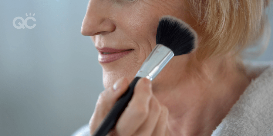 older woman applying powder to face using powder brush