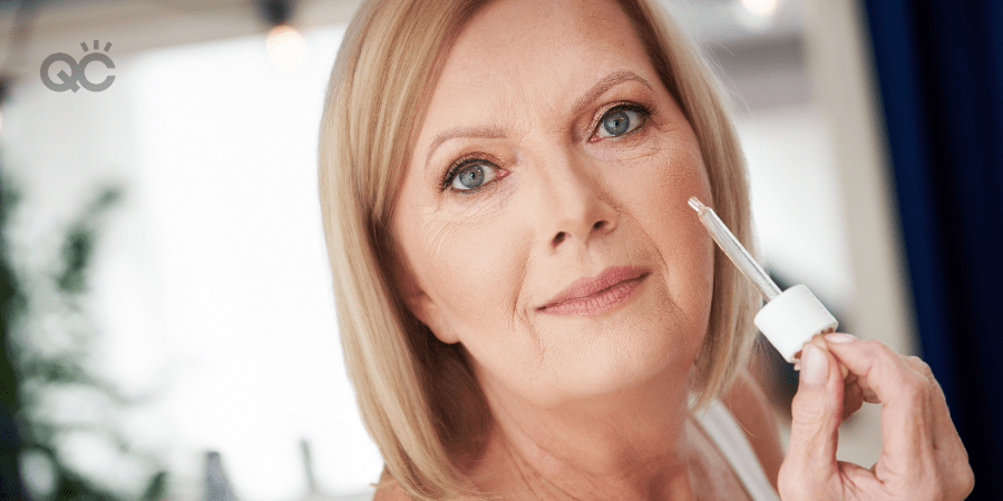 older woman applying skincare serum in cheek