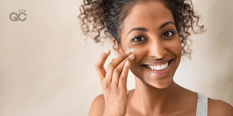 happy woman applying skincare cream to cheek