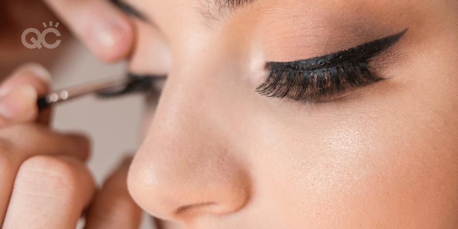 makeup artist applying eyeliner to client