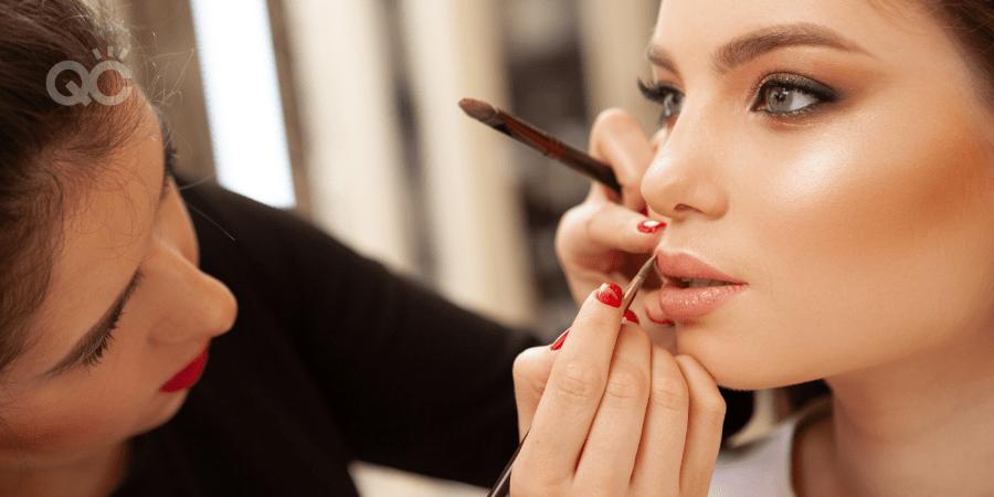 Makeup artist applying lip product on model